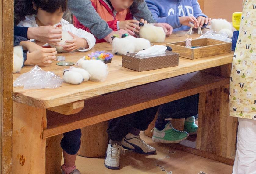 ウールクラフト教室で羊のマスコットを作る子供たち